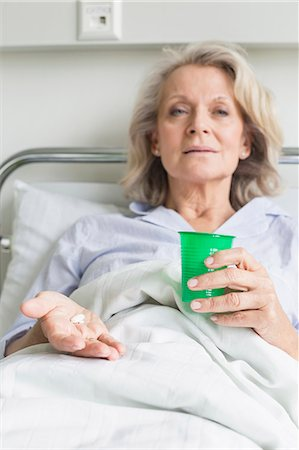 Patient in hospital holding cup and pills Stock Photo - Premium Royalty-Free, Code: 6121-07740464