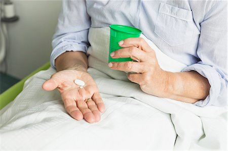 Patient in hospital holding cup and pills Stock Photo - Premium Royalty-Free, Code: 6121-07740465
