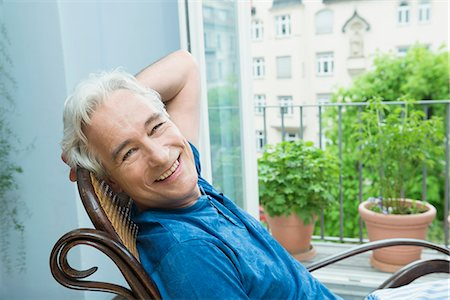 Portrait of mature man sitting in rocking chair, smiling Stock Photo - Premium Royalty-Free, Code: 6121-07740424