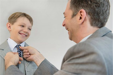 Father adjusting sons tie, smiling Stock Photo - Premium Royalty-Free, Code: 6121-07740551