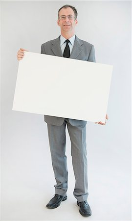 sign - Portrait of mature man holding blank whiteboard, smiling Stock Photo - Premium Royalty-Free, Code: 6121-07740557