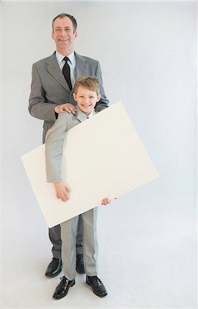 poster - Father and son holding blank whiteboard, smiling, portrait Stock Photo - Premium Royalty-Free, Code: 6121-07740554