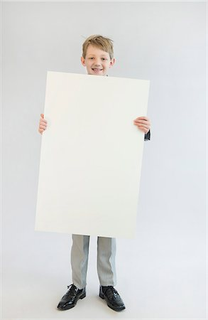 poster - Portrait of boy holding blank whiteboard, smiling Stock Photo - Premium Royalty-Free, Code: 6121-07740556