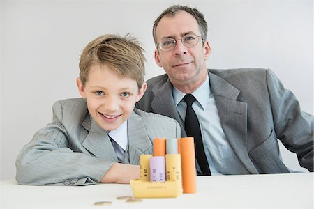 Father and son with Euro coin and coin rolls, smiling, portrait Stock Photo - Premium Royalty-Free, Code: 6121-07740558