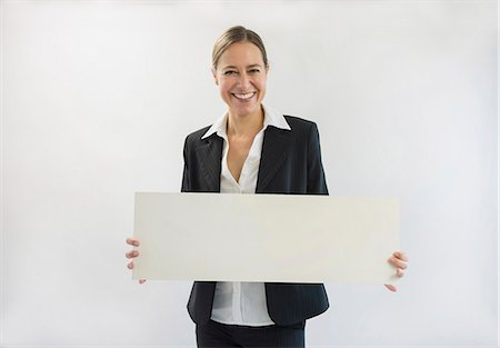 Portrait of businesswoman in black suit holding blank placard, smiling Stock Photo - Premium Royalty-Free, Code: 6121-07740693