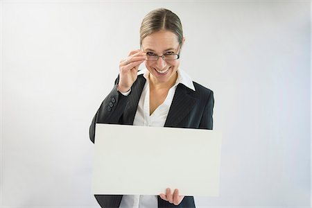poster - Portrait of businesswoman in black suit holding blank placard, smiling Stock Photo - Premium Royalty-Free, Code: 6121-07740692