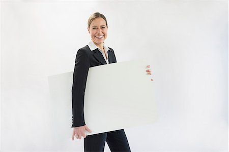 person holding sign - Portrait of businesswoman in black suit holding blank placard, smiling Stock Photo - Premium Royalty-Free, Code: 6121-07740697