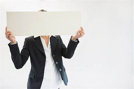 person holding sign - Businesswoman in black suit holding blank placard Stock Photo - Premium Royalty-Free, Code: 6121-07740694