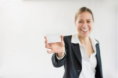 Portrait of businesswoman in black suit holding blank business card, smiling Stock Photo - Premium Royalty-Free, Code: 6121-07740695