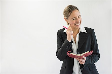 Businesswoman in black suit holding notebook and pen, smiling Stock Photo - Premium Royalty-Free, Code: 6121-07740699