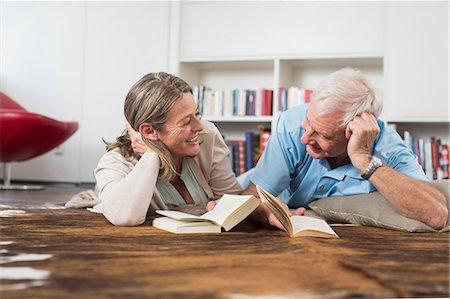 Happy couple lying on floor reading book Stock Photo - Premium Royalty-Free, Code: 6121-07740622
