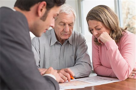 Consultant advising couple at home Stock Photo - Premium Royalty-Free, Code: 6121-07740626