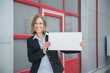 displaying - Portrait of businesswoman holding blank cardboard, smiling Stock Photo - Premium Royalty-Free, Code: 6121-07740766