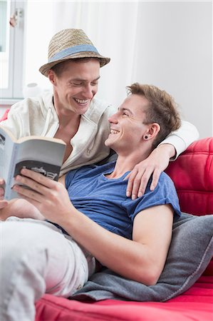Homosexual couple sitting on couch with book, smiling Stock Photo - Premium Royalty-Free, Code: 6121-07740786