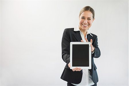 displaying - Portrait of businesswoman in black suit holding digital tablet, smiling Stock Photo - Premium Royalty-Free, Code: 6121-07740701