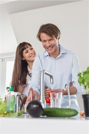 property release - Couple in kitchen, man washing tomatos at water tab Stock Photo - Premium Royalty-Free, Code: 6121-07740711