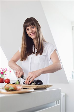 Portrait of mid adult woman cutting aubergine in kitchen, smiling Stock Photo - Premium Royalty-Free, Code: 6121-07740718