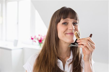 Portrait of mid adult woman smelling wine cork Stock Photo - Premium Royalty-Free, Code: 6121-07740724