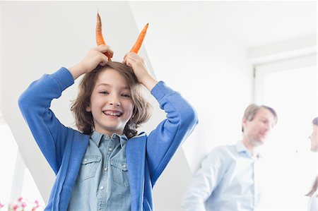 Portrait of girl making devil with carrots as horns, smiling Stock Photo - Premium Royalty-Free, Code: 6121-07740736