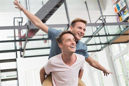 Homosexual couple giving piggyback ride, smiling Stock Photo - Premium Royalty-Free, Code: 6121-07740815