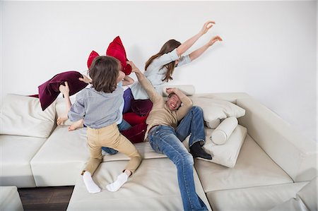 Family doing pillow fight on couch Stock Photo - Premium Royalty-Free, Code: 6121-07740949