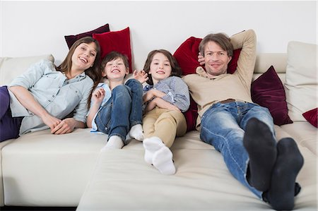 pantyhose kid - Portrait of family lying on couch, smiling Stock Photo - Premium Royalty-Free, Code: 6121-07740953