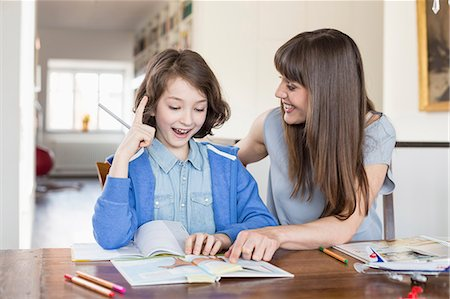 student (female) - Mother helping daughter in homework, smiling Stock Photo - Premium Royalty-Free, Code: 6121-07740930