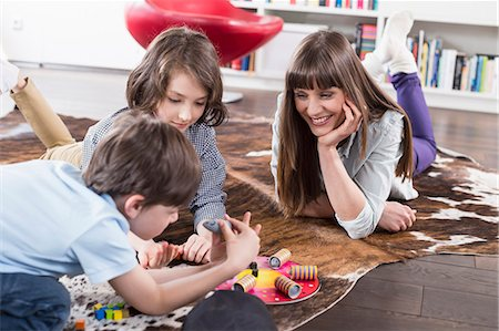 red chair - Mother playing board game with her children Stock Photo - Premium Royalty-Free, Code: 6121-07740937