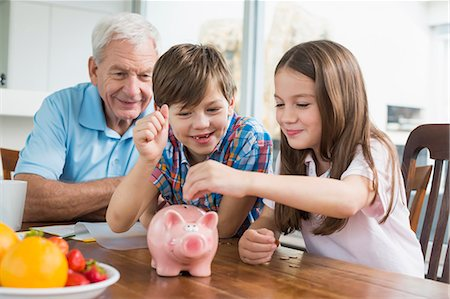 Two children and grandfather with piggy bank Stock Photo - Premium Royalty-Free, Code: 6121-07741059