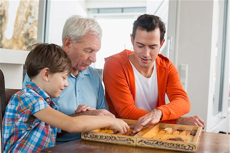 Grandfather, father and son playing backgammon Stock Photo - Premium Royalty-Free, Code: 6121-07741066