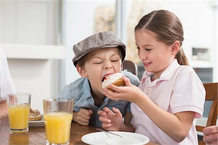 Playful brother and sister eating cake Stock Photo - Premium Royalty-Free, Code: 6121-07741073