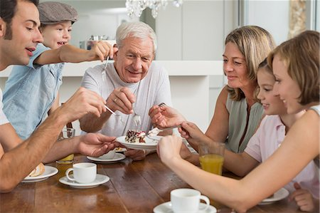family table eating together - Extended family at table eating cake Stock Photo - Premium Royalty-Free, Code: 6121-07741074