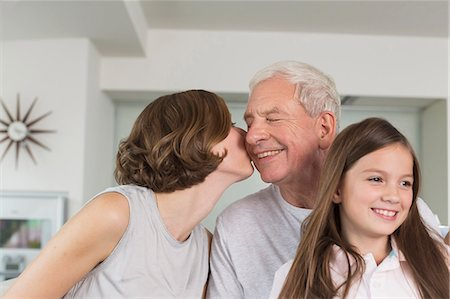 Adult daughter kissing father with granddaughter at their side Stock Photo - Premium Royalty-Free, Code: 6121-07741085