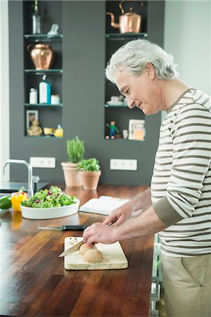 Mature man cutting vegetable on chopping board in kitchen, smiling Stock Photo - Premium Royalty-Free, Code: 6121-07741092