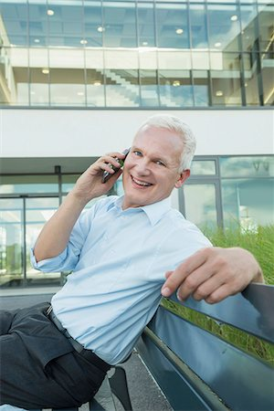 portrait of businessman sitting on a bench using his smartphone Stock Photo - Premium Royalty-Free, Code: 6121-07741031
