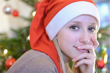 Portrait of teenage girl in front of christmas tree Stock Photo - Premium Royalty-Free, Code: 6121-07741148