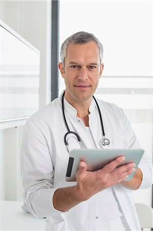 Doctor holding digital tablet, portrait Stock Photo - Premium Royalty-Free, Code: 6121-07741207