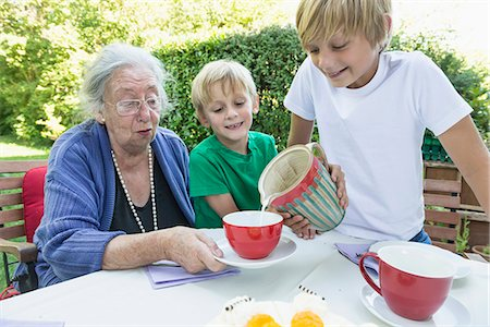 Grandson pouring milk in his grandmothers cup Stock Photo - Premium Royalty-Free, Code: 6121-07741213