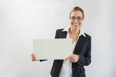Portrait of businesswoman in black suit holding blank placard, smiling Stock Photo - Premium Royalty-Free, Code: 6121-07741359