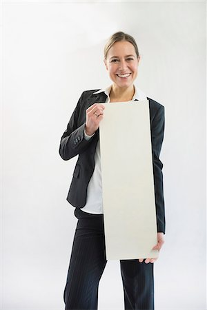 poster - Portrait of businesswoman in black suit holding blank placard, smiling Stock Photo - Premium Royalty-Free, Code: 6121-07741360