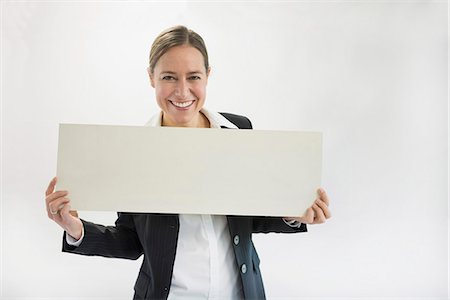 poster - Portrait of businesswoman in black suit holding blank placard, smiling Stock Photo - Premium Royalty-Free, Code: 6121-07741361