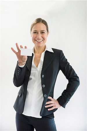 Portrait of businesswoman in black suit holding blank business card, smiling Stock Photo - Premium Royalty-Free, Code: 6121-07741362