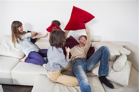 Family doing pillow fight on couch Stock Photo - Premium Royalty-Free, Code: 6121-07741387