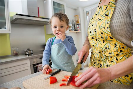 Son nibbling vegetables while mother is cutting them Stock Photo - Premium Royalty-Free, Code: 6121-07741394