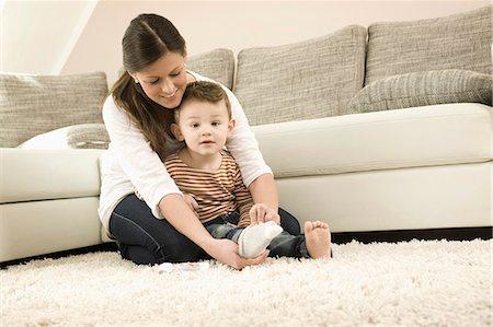 pantyhose kid - Mother putting socks on son, smiling Stock Photo - Premium Royalty-Free, Code: 6121-07741445