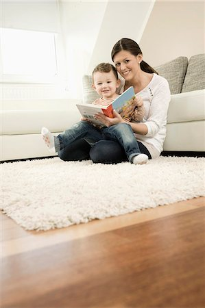 story - Mother and son are watching storybook, smiling Stock Photo - Premium Royalty-Free, Code: 6121-07741453