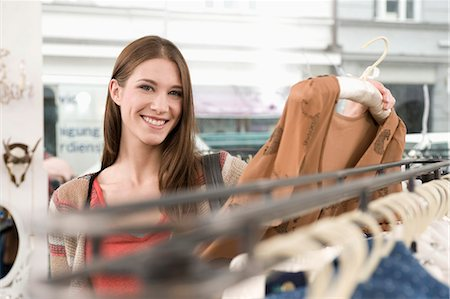 selecting - Portrait of young woman shopping in fashion store, smiling Stock Photo - Premium Royalty-Free, Code: 6121-07741468