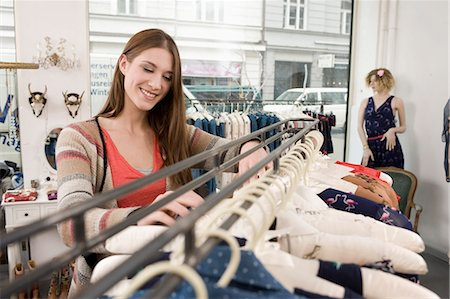 selecting - Young woman shopping in fashion store, smiling Stock Photo - Premium Royalty-Free, Code: 6121-07741470