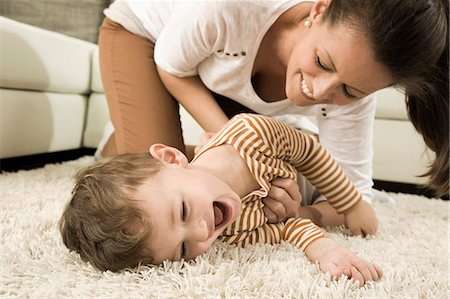 playing - Mother and son are romping in living room, smiling Stock Photo - Premium Royalty-Free, Code: 6121-07741479