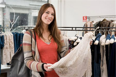 Portrait of young woman shopping in fashion store, smiling Stock Photo - Premium Royalty-Free, Code: 6121-07741482